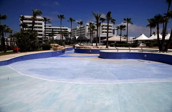 A swimming pool lays empty at a closed hotel at the Cyprus seaside resort of Ayia Napa, a favourite among tourists from Europe and beyond. (AP Photo/Petros Karadjias)