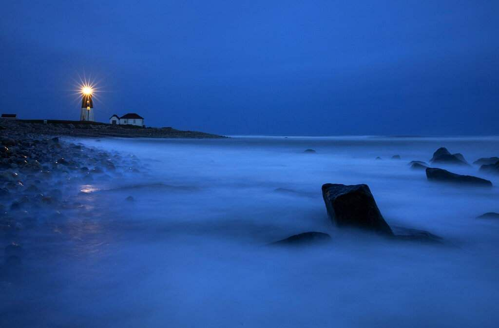 Waves wash over rocks as a beacon of light shines across the rocky shore from the Point Judith Lighthouse in Narragansett, Rhode Island. (AP Photo/David Goldman)