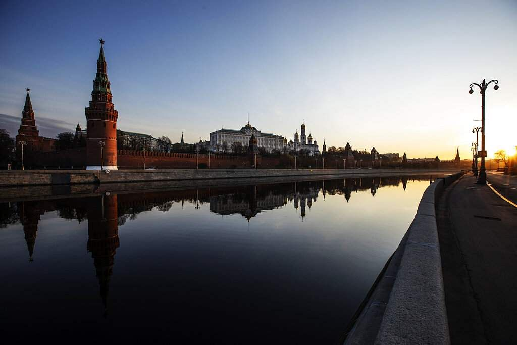 The Kremlin and its towers and churches are reflected in the Moscow River along a deserted embankment as the sun rises over Moscow, Russia. (AP Photo/Alexander Zemlianichenko)