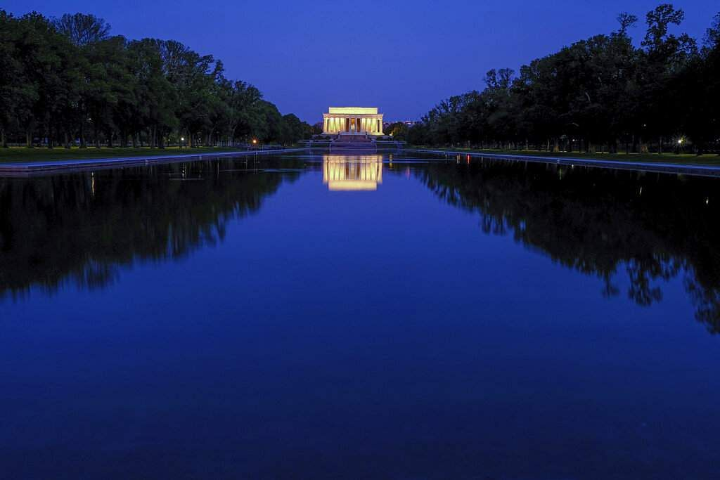 The Lincoln Memorial is reflected in the still waters of the reflecting pool on the National Mall in Washington before dawn. (AP Photo/J David Ake)