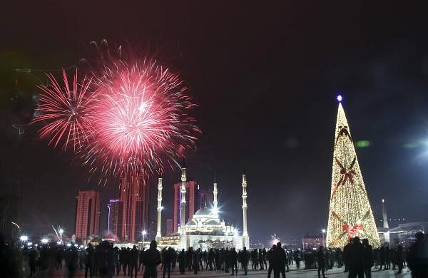 Fireworks explode over a not-too-crowded square with a Christmas tree and and the main mosque during New Year's celebrations in Grozny, Russia AP20366798067597