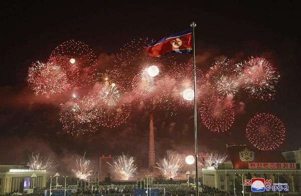 Fireworks illuminate the night sky, marking the New Year, as crowds of people look on, at Kim Il Sung Square in Pyongyang, North KoreaAP21001132811501
