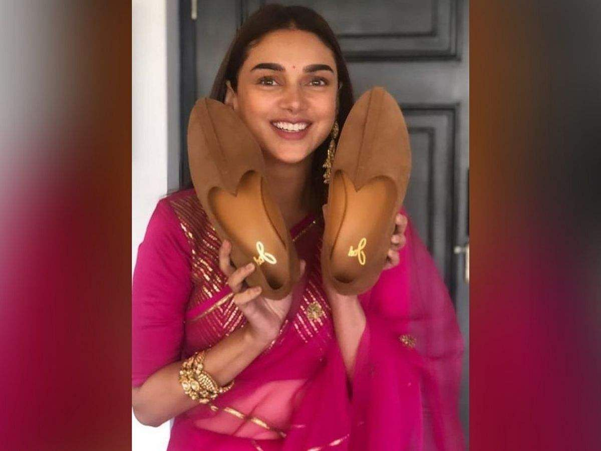 Aditi Rao Hydari holding Vaibhav Rekhi's shoes for the joota chhupai ritual. Courtesy: Instagram