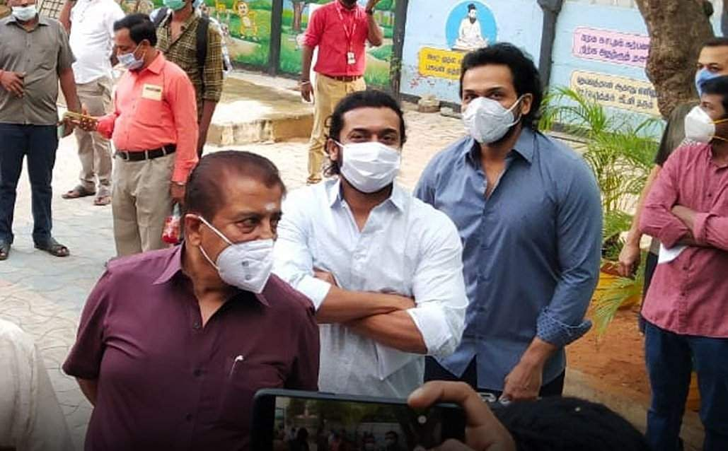 Actor Suriya, his brother Karthi and father Sivakumar wait in line to cast their votes